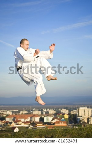 Young adult men practicing Karate outdoor, city in background - stock photo