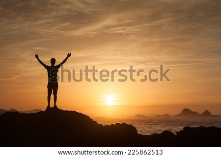 Young adult raising arms to the sea at sunset hands up - stock photo