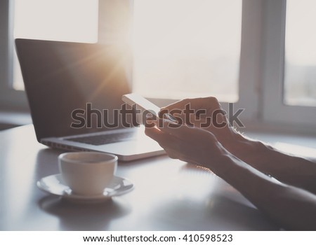 Young adult using smartphone in the office - stock photo