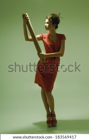 Young adult woman holding curl of paper, film grain is added for better impression - stock photo