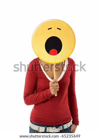 young adult woman holding emoticon, yawning on white background. Vertical shape, waist up - stock photo
