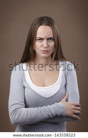 Young adult woman looking at camera displeased and angry - stock photo