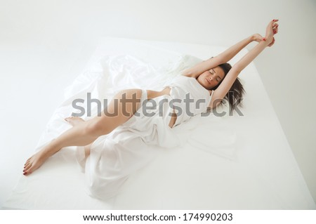 Young adult woman strech on bed in morning - stock photo