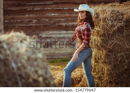 young adult woman wearing country style posing on farmland, closeup portrait - stock photo