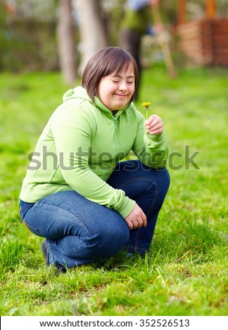 young adult woman with disability enjoying nature in spring garden - stock photo