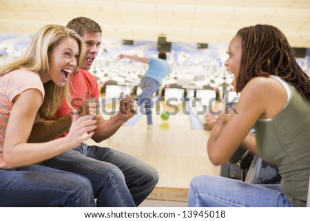 Young adults cheering in a bowling alley - stock photo