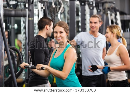 Young adults doing powerlifting on machines at a fitness club  - stock photo