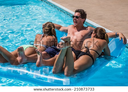 Young adults lying on raft having fun in swimming pool during summer. - stock photo