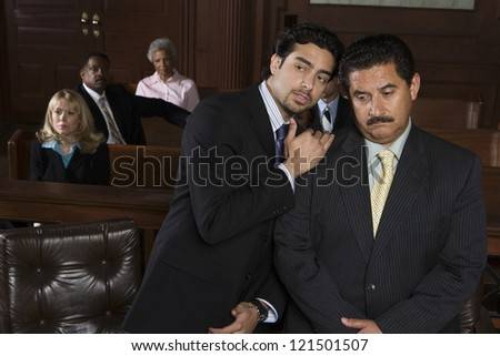 Young advocate sharing a point with client with people sitting in the courtroom - stock photo
