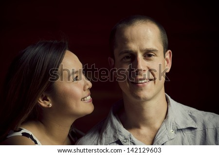 Young affectionate couple with attractive woman looking at her partner. Male is caucasian, female is asian. - stock photo
