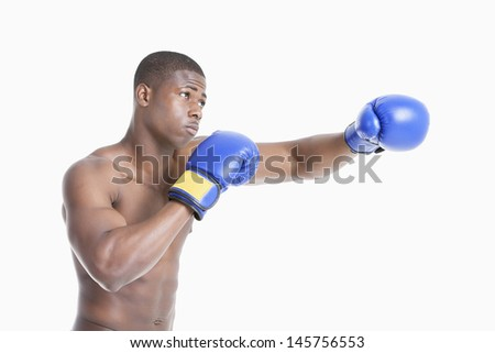 Young African American boxer boxing over gray background - stock photo