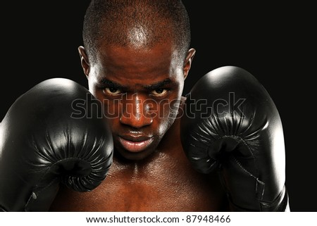 Young African American Boxer wearing gloves isolated on a dark background - stock photo