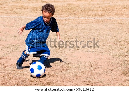 Young African American boy playing soccer. - stock photo