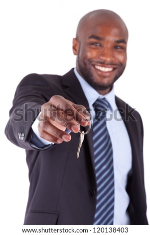 Young African American businessman holding a house key, isolated on white background - stock photo