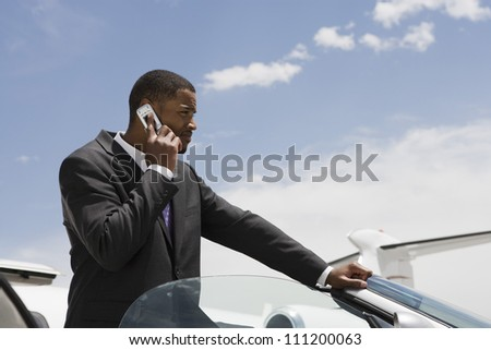 Young African American businessman on a call by car at airfield - stock photo