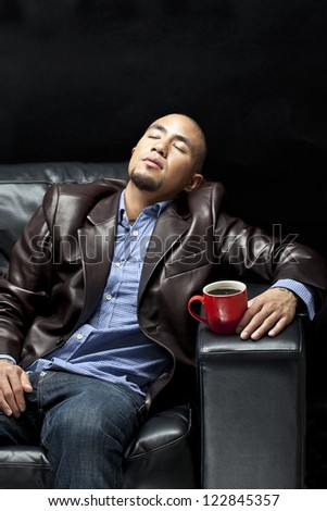 Young African American businessman relaxing on a couch with a cup of coffee, - stock photo