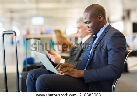 young african american businessman using laptop while waiting for his flight - stock photo