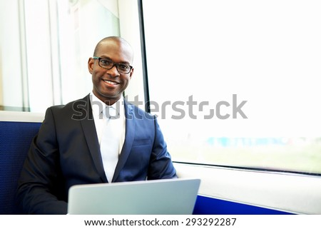 Young African American Businessman with Laptop Computer, Smiling at the Camera While Commuting on a Train - stock photo