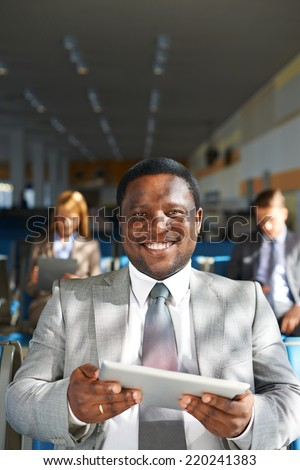 Young African-american businessman with touchpad looking at camera with two colleagues on background - stock photo