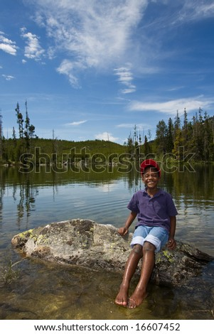 Young African American child playing in a lake at Yellowstone National Park in Wyoming, USA. - stock photo