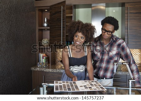 Young African American couple at new furnished kitchen - stock photo