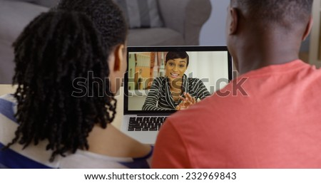 Young African American couple talking to sister over web chat - stock photo