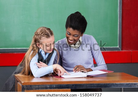 Young African American female teacher and schoolgirl reading together at desk in classroom - stock photo