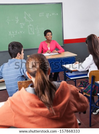 Young African American female teacher and teenage students sitting in classroom - stock photo
