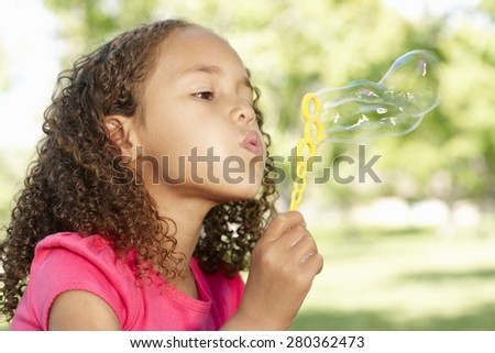 Young African American Girl Blowing Bubbles In Park - stock photo