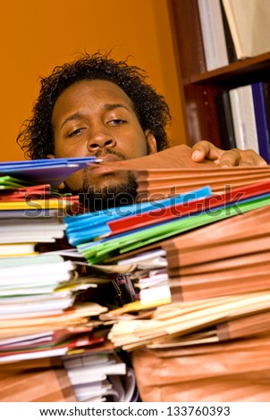 Young African American Male Buried in Work - stock photo