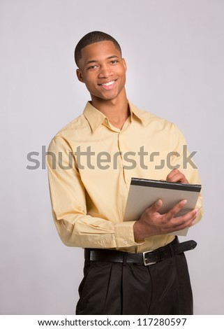 Young African American Male Writing on Notepad on Grey Background - stock photo