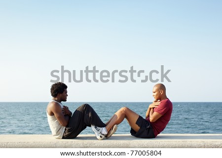 young african american man and hispanic friend doing series of sit-ups along the Caribbean sea in Havana, Cuba. Horizontal shape, full length, side view, copy space - stock photo