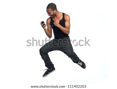 Young African American man listening to his mp3 player and jumping and dancing. Isolated on white background - stock photo