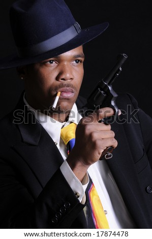 young African American man posing as a gangster - stock photo