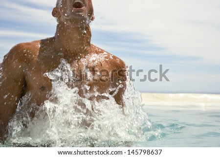 Young African American man surfacing in swimming pool - stock photo