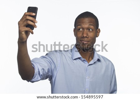 Young African-American man taking a picture of himself with smartphone, horizontal  - stock photo