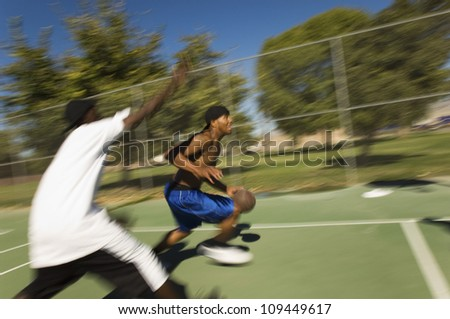 Young African American men playing basketball - stock photo