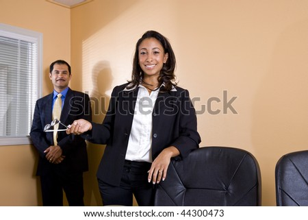 Young African-American office worker standing in boardroom with middle-aged Hispanic manager smiling in background - stock photo
