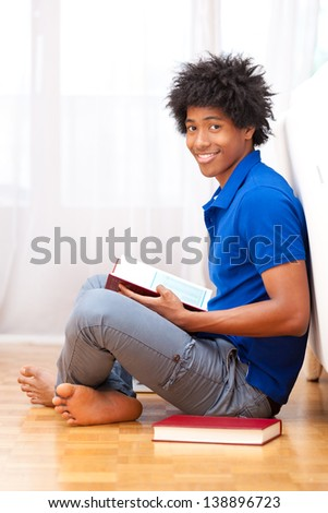 Young african american student seated on the floor reading books - African people - stock photo