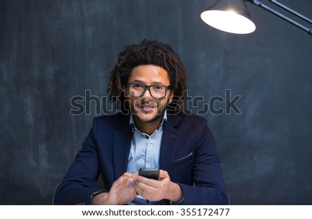 Young African American student standing against a blank chalkboard, using phone - stock photo