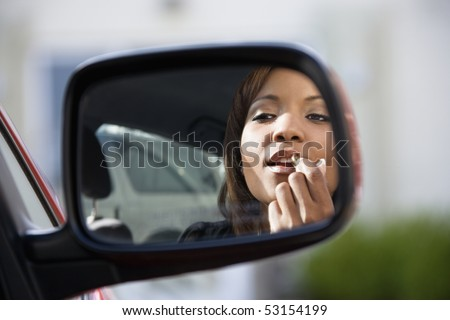 Young African American woman applying lipstick looking at reflection in car mirror. - stock photo