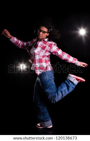 Young African American woman dancing, over black background - stock photo