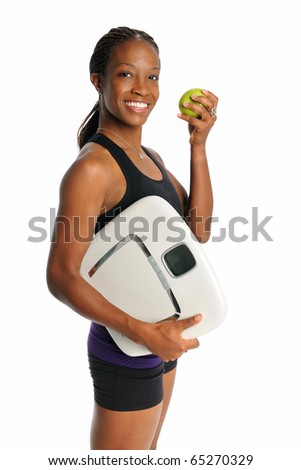 Young African American woman holding weight scale and apple isolated over white background - stock photo