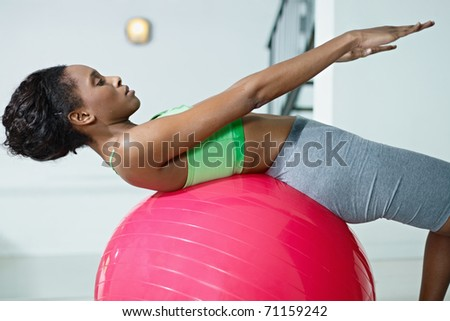 young african american woman in green sportswear exercising abdominals on fit ball in gym. Horizontal shape, side view, three quarter length - stock photo