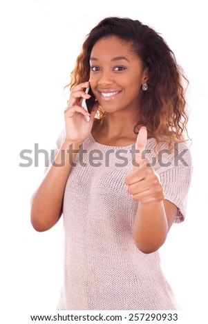 Young African American woman making a phone call on her smartphone making thumbs up gesture - stock photo