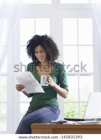 Young African American woman reading document with a coffee cup on desk - stock photo