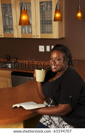 Young African-American Woman Reading the Bible and Drinking Coffee - stock photo