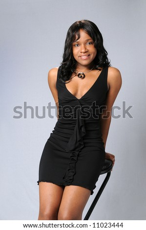 Young African American woman sitting on edge of stool - stock photo