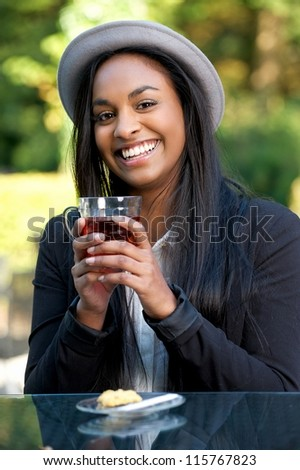 Young African American woman smiling and enjoying a cup of tea - stock photo
