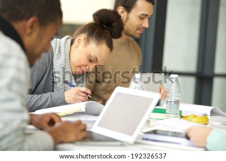 Young african american woman taking notes from books for her study. Students sitting at table with books and laptop studying. - stock photo